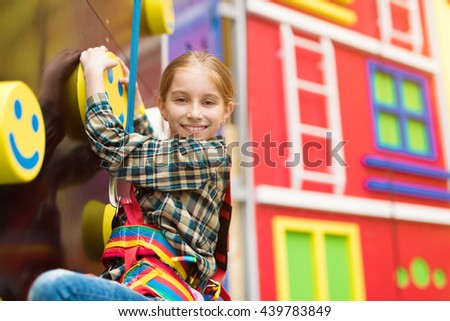 smiling little girl on climbing wall in entertainment center - stock photo