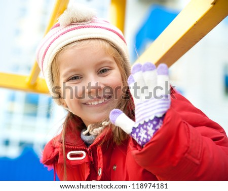 Smiling little girl on outdoor playground equipment - stock photo