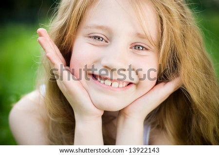 Smiling little girl outside in green grass - stock photo
