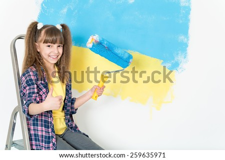 Smiling little girl painting big Ukrainian flag on wall at home - stock photo