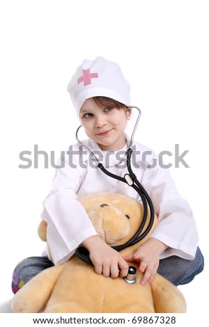 smiling little girl playing doctor with her toy bear - stock photo
