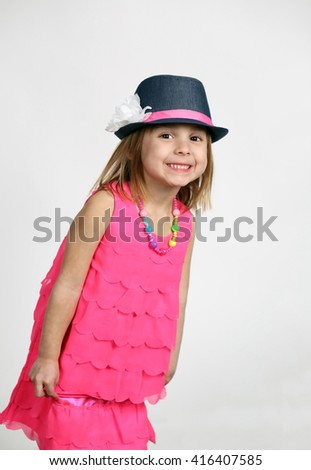 smiling little girl playing dress up