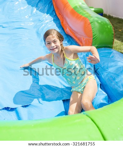 Smiling little girl playing on an inflatable slide bounce house - stock photo