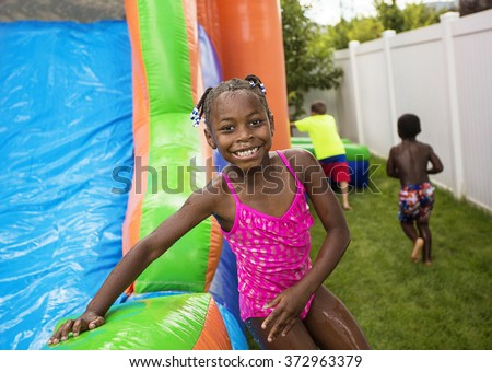 Smiling little girl playing outdoors on an inflatable bounce house  - stock photo