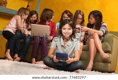Smiling little girl playing video game on portable console with her friends - stock photo