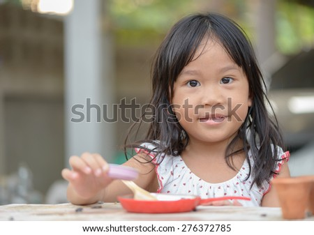 Smiling little girl plays cook on the table