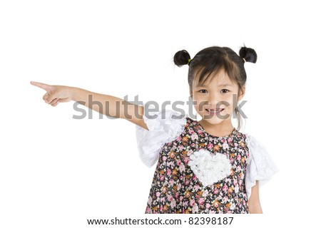 smiling little girl pointing to the side, isolated on white background - stock photo