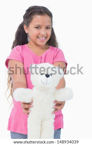 Smiling little girl showing her teddy bear to camera in white background - stock photo