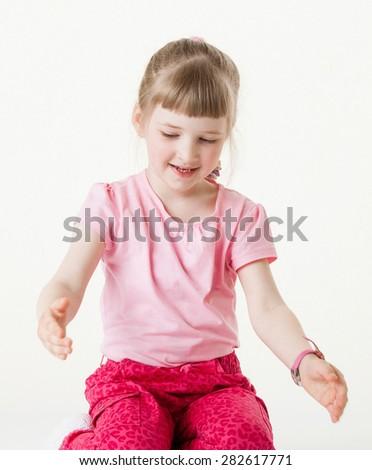 Smiling little girl showing something large size, white background - stock photo