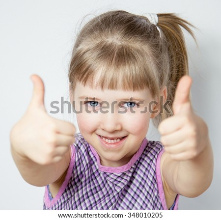 Smiling little girl showing thumbs up - closeup portrait - stock photo
