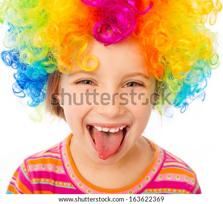 smiling little girl shows tongue in clown wig isolated on white background - stock photo