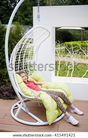 Smiling little girl sits in white swing hanging on chain in summer park. - stock photo