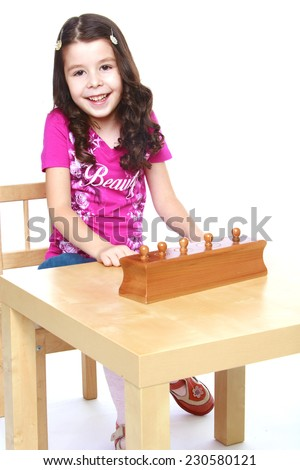 smiling little girl sitting at the table and working with Montessori materials, isolated on a white background.Isolated on white background. - stock photo