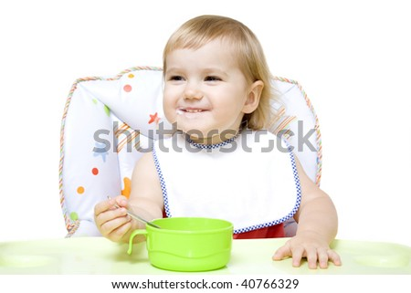 Smiling little girl sitting in baby chair and eating 16-22 months