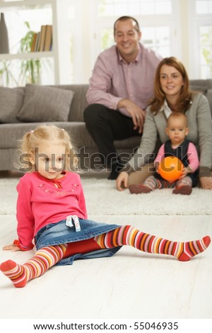 Smiling little girl sitting in straddle on living room floor, with family in background.