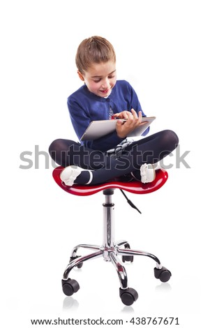 Smiling little girl sitting on a chair and using a tablet computer, isolated on white background