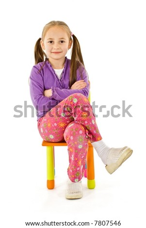 Smiling little girl sitting on a small chair - stock photo