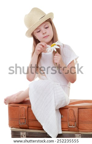 Smiling little girl sitting on a suitcase - stock photo