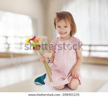smiling little girl sitting on her knees and holding a bouquet of flowers.kindergarten, the concept of childhood and joy, teens