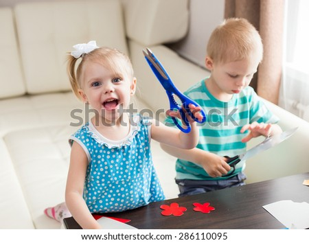 smiling little girl sitting on the couch at the table with colored cardboard shows large scissors and laughing - stock photo