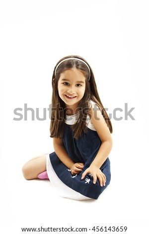 Smiling little girl sitting on the floor. Isolated on white background  - stock photo