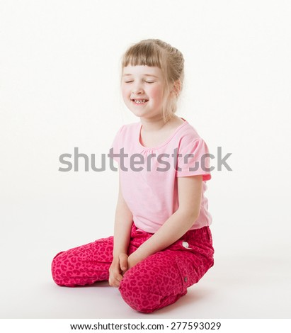 Smiling little girl sitting on the floor with closed eyes, white background - stock photo