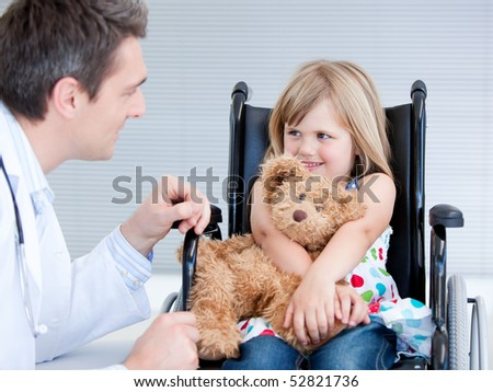 Smiling little girl sitting on the wheelchair lokking at the doctor in the hospital