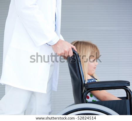 Smiling little girl sitting on the wheelchair supported by a doctor at the hospital - stock photo