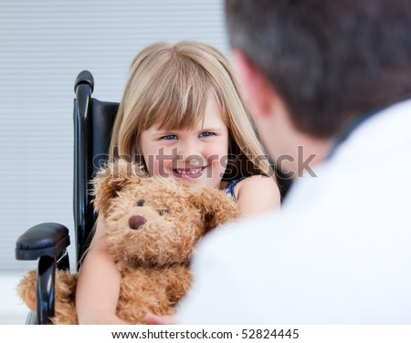 Smiling little girl sitting on the wheelchair with her teddy bear at the hospital - stock photo