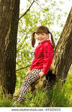 Smiling little girl sitting on tree in forest - stock photo