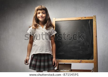 Smiling little girl standing beside a blackboard - stock photo