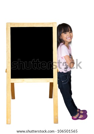 Smiling little girl standing beside a blackboard, Isolated on white - stock photo