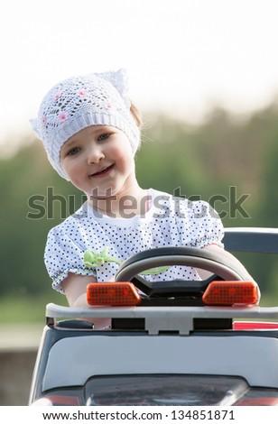 Smiling little girl steers electromobile - stock photo