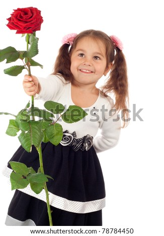Smiling little girl stretching forward red rose - stock photo