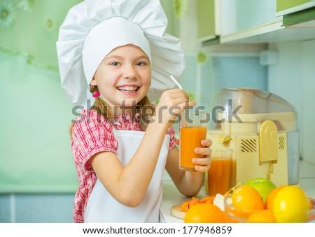 Smiling little girl tastes freshly prepared apple-carrot juice - stock photo