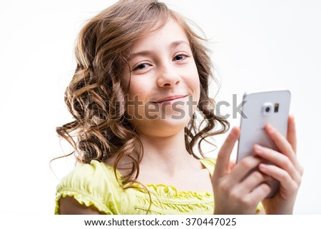 smiling little girl using a smartphone