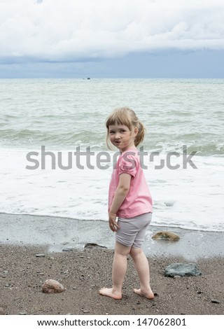 Smiling little girl walking near the seashore