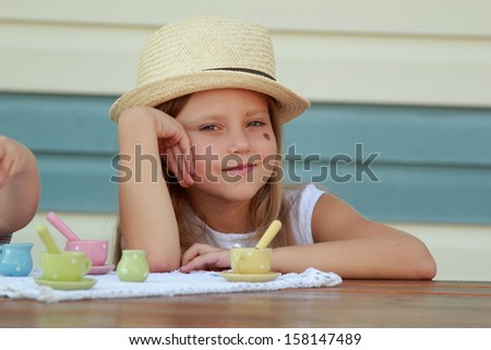 Smiling little girl with beautiful long blond hair wearing a straw hat playing with toy dishes for tea outdoors - stock photo