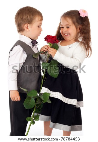 Smiling little girl with boy and red rose - stock photo