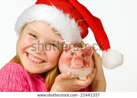 Smiling little girl with christmas hat holding piggy bank - stock photo