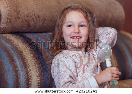 Smiling little girl with cough using inhaler at home - stock photo