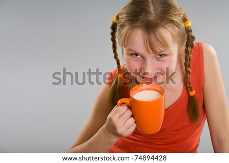 Smiling little girl with cup of milk - stock photo