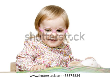 Smiling little girl with glasses viewing children book