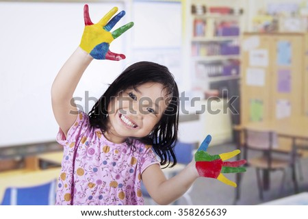 Smiling little girl with hands painted in colorful paints on classroom - stock photo