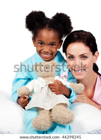 Smiling little girl with her nurse looking at the camera against a white background