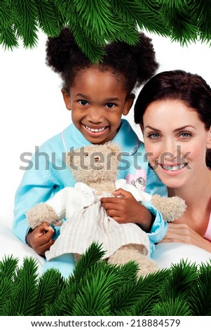 Smiling little girl with her nurse looking at the camera against fir tree branches forming frame - stock photo