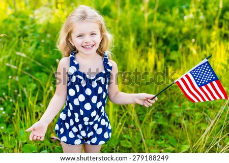 Smiling little girl with long curly blond hair holding american flag and waving it, outdoor portrait on sunny day in summer park. Independence Day, Flag Day concept