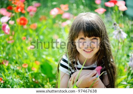 Smiling little girl with long dark hair sitting on poppy field - stock photo