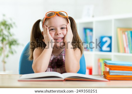 smiling little girl with opened book indoors - stock photo