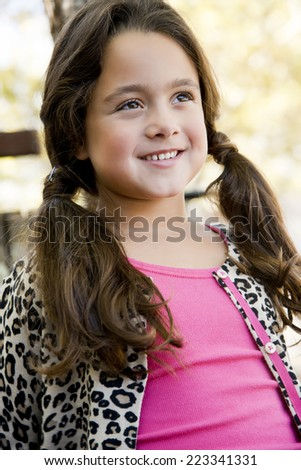 Smiling little girl with pigtails, outside, looking away, 7 yrs old - stock photo